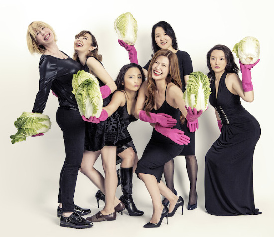 The Crazy Korean Cooking team laughing and holding cabbages